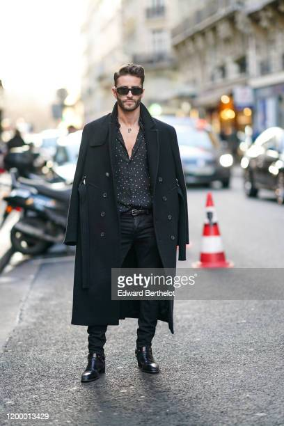 Pelayo Diaz wears sunglasses, a black long coat, an open shirt with polka dots, black pants, leather boots, outside Rochas, during Paris Fashion Week...
