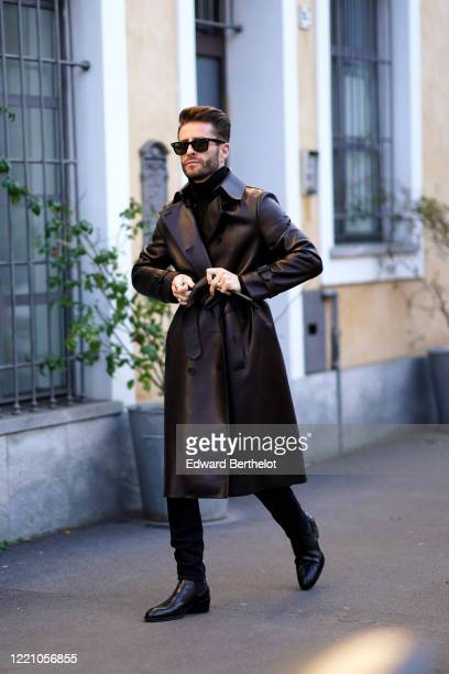 Pelayo Diaz wears sunglasses, a turtleneck pullover, a black leather long coat, black leather shoes, outside Tod's, during Milan Fashion Week...