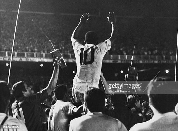 Pele is lifted up by his Santos team mates after scoring the 1000th goal of his career during a game against Vasco da Gama at the Maracana Stadium...