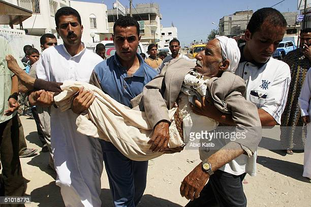 Pelestinian men carry their grieving relative to mourn over the body of his 25 yearold nephew Yassir alArja a scrap dealer from Rafah's Brazil...