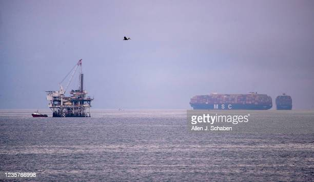 Pelican flies over the Pacific Ocean with a view of Oil Rig platform Esther and large container ships anchored off the coast Thursday, Oct. 7, 2021...