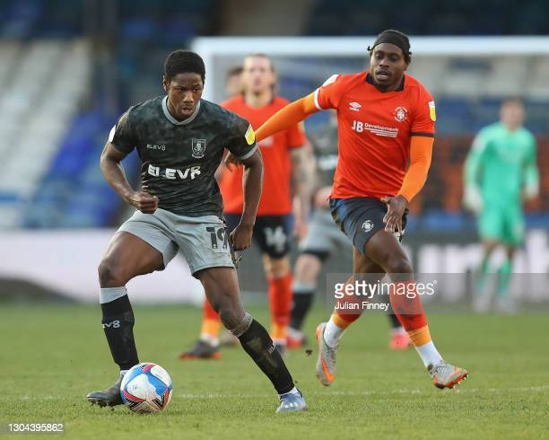 Pelly-Ruddock Mpanzu of Luton in action against Osaze Urhoghide of Sheffield Wednesday during the Sky Bet Championship match between Luton Town and...