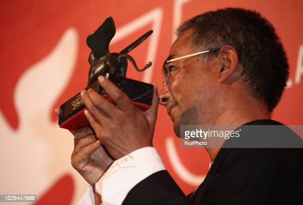 Pema Tseden poses with Orizzonti Award for Best Screenplay Award forJinpa at the Winners Photocall during the 75th Venice Film Festival on September...
