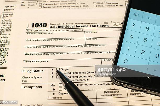 A pen a smart phone calculator and Form 1040 tax document