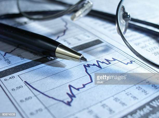 Pen and glasses on stock chart.
