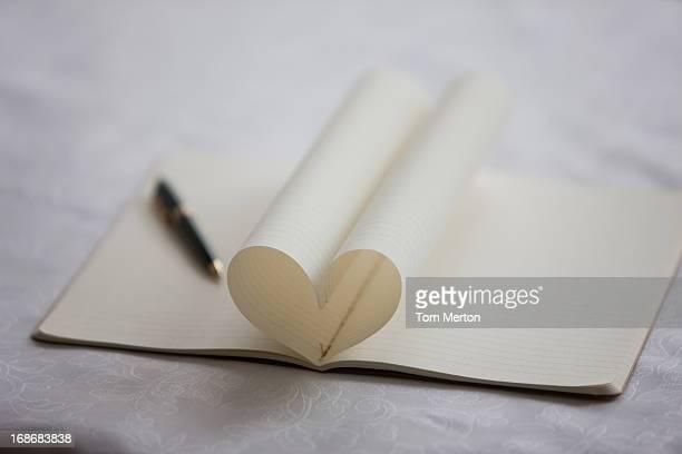Stylo et page de cahier formant en forme de cœur