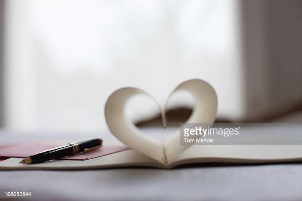 pen and pages of notebook forming heart-shape - love letter stock photos and pictures
