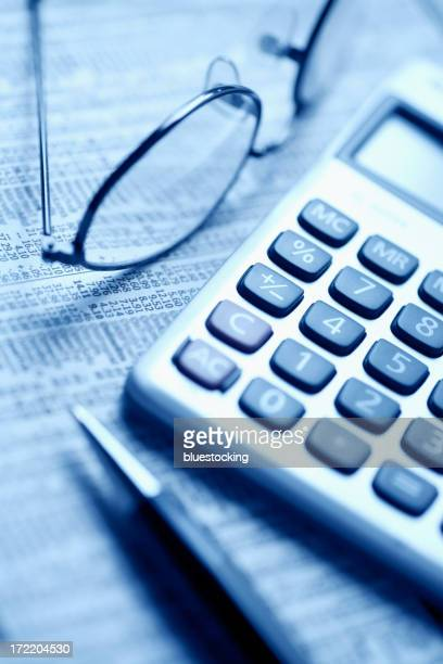 Pen glasses and calculator representing stock market data