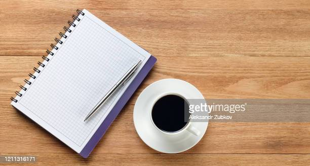a pen on a blank sheet of notepad and a mug of black coffee on a wooden table. items of a businessman or manager in the workplace. - elektronische organiser stockfoto's en -beelden