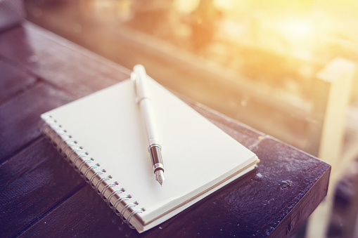 pen on the desk,Open a blank white notebook on wooden table and green bokeh background ,vintage color,selective focus 1049601994