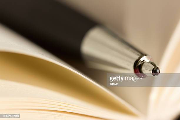 pen placed inside notebook - lutavia stock pictures, royalty-free photos & images