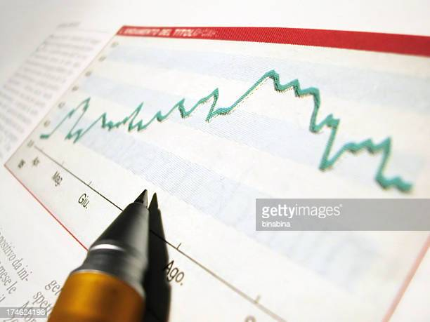 pen tip on a magazine showing graph of economy growth - annual event stock pictures, royalty-free photos & images