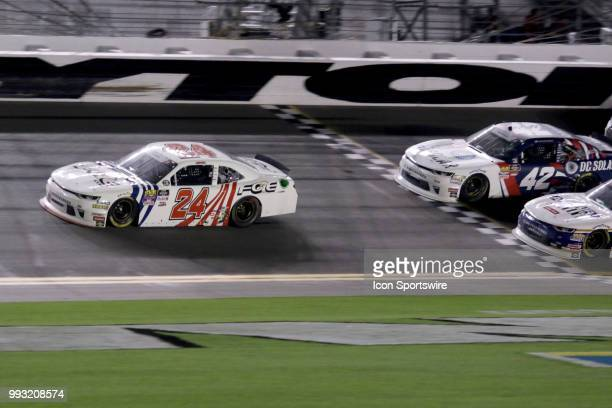 Penalized Justin Haley crosses the finish line first in front of winner Kyle Larson and Elliott Sadler at the end of the CocaCola Firecracker 250...