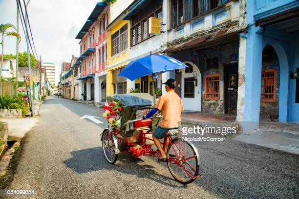 penang man drives a rickshaw in george town's historic district - george town penang stock photos and pictures