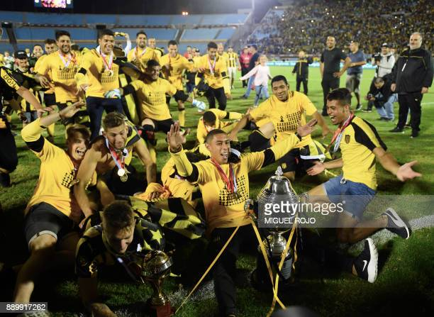 Penarol players celebrate after winning their 2017 Uruguayan Championship final match against Defensor at the Centenario Stadium in Montevideo on...