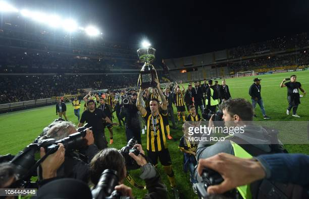Penarol's captain Fabian Estoyanoff lifts the trophy after obtaining the Uruguayan Clausura football tournament after defeating Progreso 10 with a...