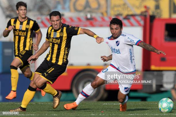 Penarol's Maxi Rodriguez vies for the ball with Nacional's Tabare Viudez during Uruguay's football derby at the Centenario stadium in Montevideo on...