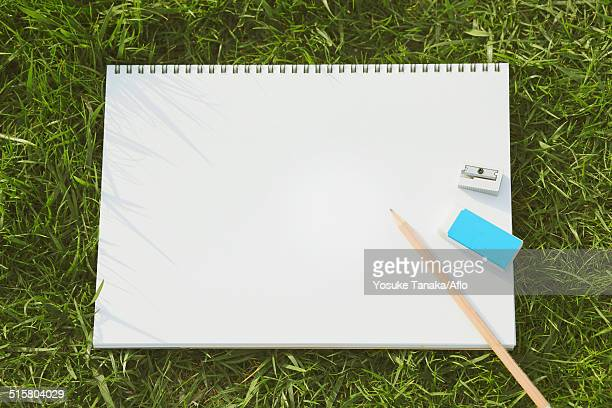 Pencil and sketchbook on grass