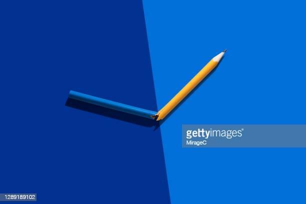 pencil cracked into two colors - farbquadrat stock-fotos und bilder