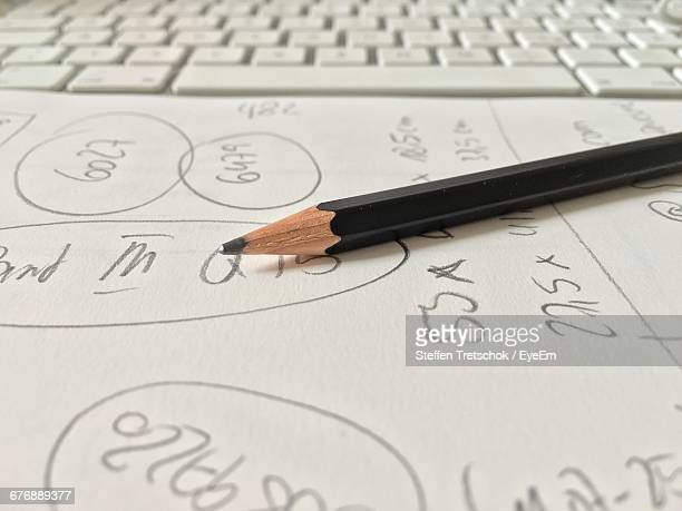 Pencil On Paper With Financial Calculations By Laptop Keypad