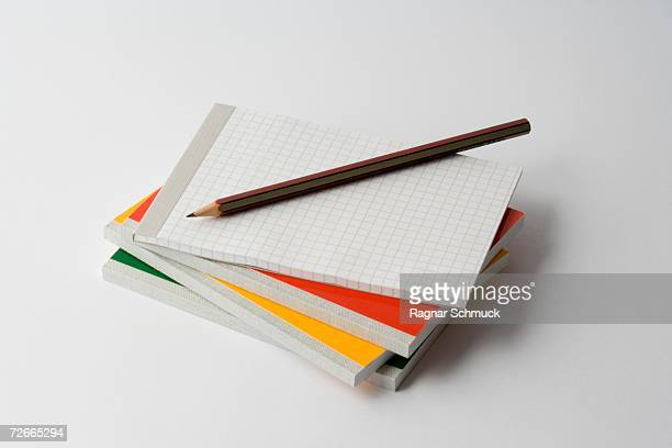 pencil on top of stack of note pads - workbook stock photos and pictures