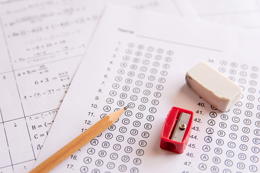 Pencil, Sharpener and eraser on answer sheets or Standardized test form with answers bubbled. multiple choice answer sheet 949490402