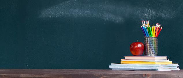 Pencil tray and an apple on notebooks on school teacher's desk 1164371092