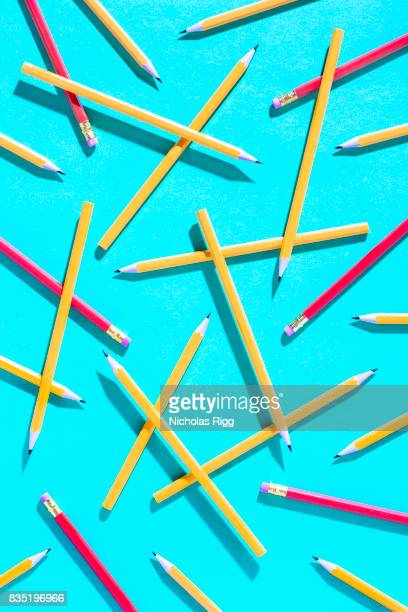 Pencils and shadows cast on blue background