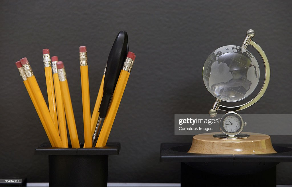 Pencils in cup and globe clock on desk : Stockfoto