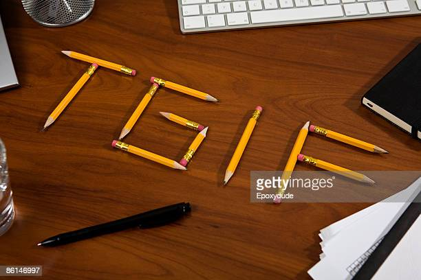 Pencils on a desk arranged to spell TGIF