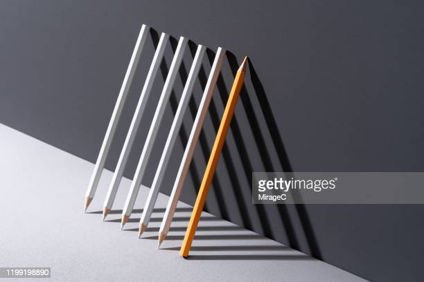 pencils with shadow triangle shape - standing out from the crowd stock pictures, royalty-free photos & images