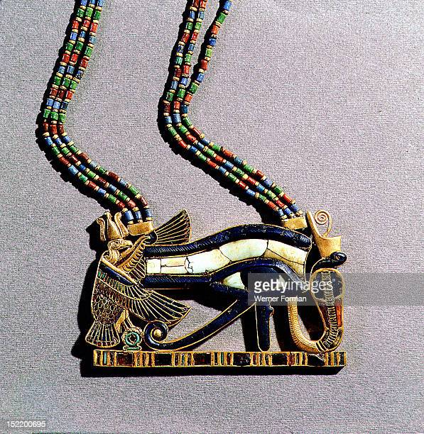 A pendant from the tomb of Tutankhamun in the form of a Wedjat eye symbol of protection flanked by the vulture goddess Nekhbet and the snake goddess...
