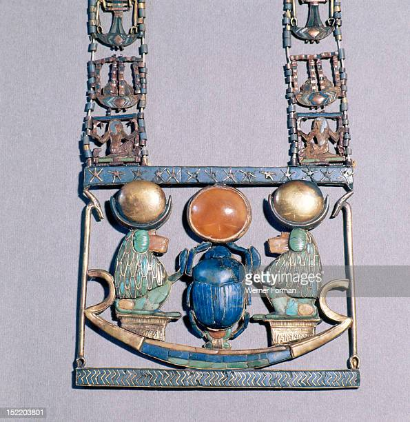 Pendant from the tomb of Tutankhamun, Two baboons with moon discs on their heads worship the sun god in scarab beetle form. He holds up a solar disc...