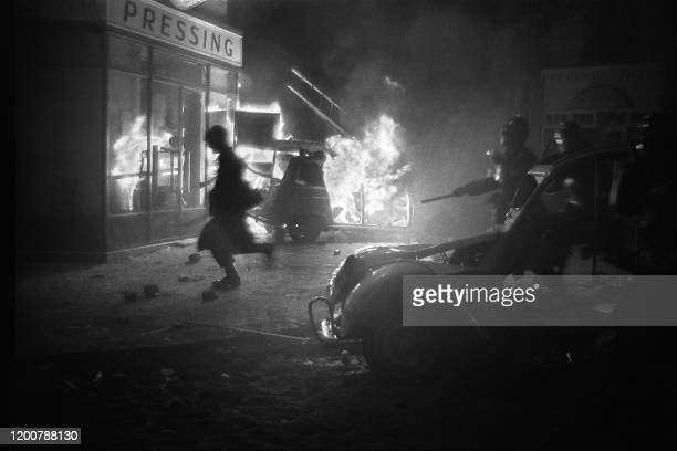 Pendant la nuit d'émeutes du 10 au 11 mai 1968, à Paris, au Quartier latin, des éléments des forces de l'ordre chargent tandis qu'une automobile...