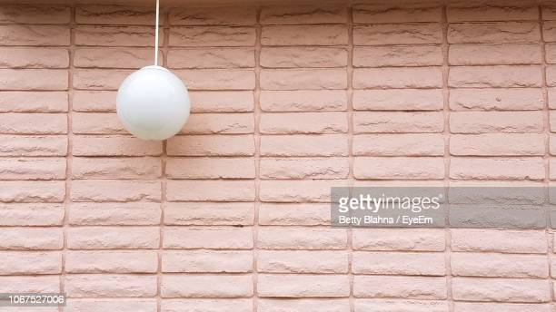 pendant light hanging against brick wall - pendant light stock pictures, royalty-free photos & images