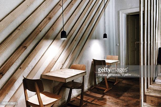 Pendant Lights Hanging Over Wooden Chairs And Tables