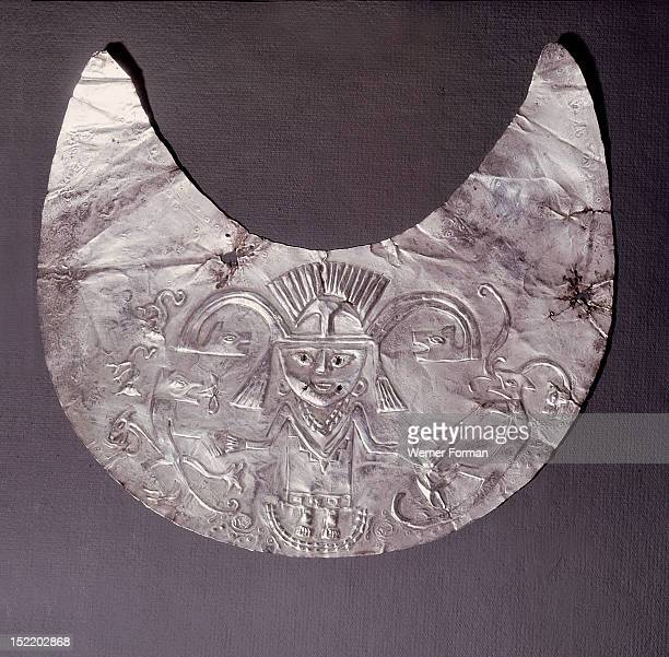 Pendant made from a thin sheet of hammered silver, Depicted is a Chimu lord or god wearing an elaborate feathered axe headdress and a poncho. Fierce...