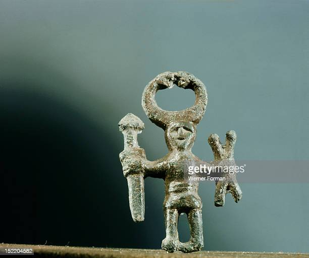 Pendant or amulet of a man holding a sword and two spears and wearing a horned helmet Probably represents a priest of the cult of Odin Sweden Viking...