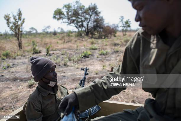 Pendjari National Park rangers sit on the back of a vehicle during an elephant collaring exercise at Pendjari National Park near Tanguieta on January...