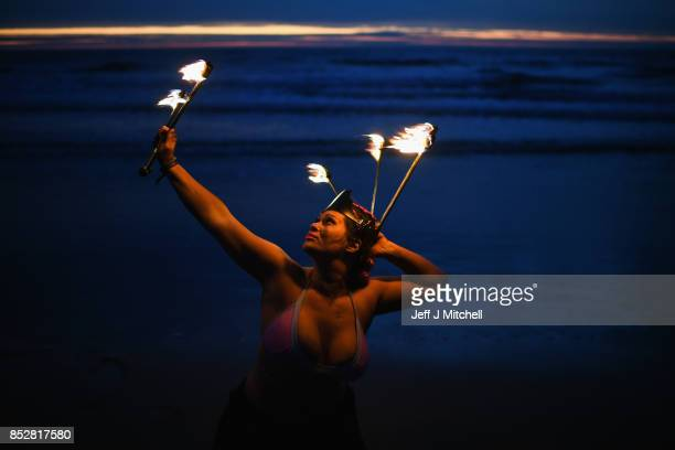 Penella Bee from Sunderland performs with fire before naked bathers enter the water during the North East Skinny Dip at Druridge bay on September 25...