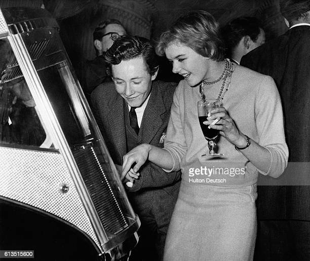 Penelope Allsop and Greville Howard choose a song on the jukebox at Dorothy's Club