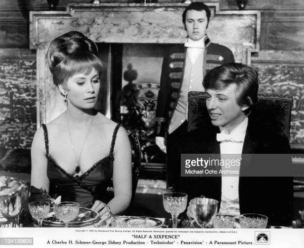 Penelope Horner and Tommy Steele sitting at the dining table together in a scene from the film 'Half A Sixpence' 1967