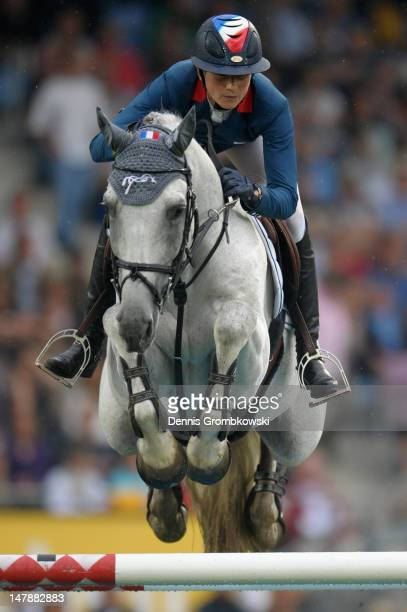 Penelope Leprevost of France and her horse Mylord Carthago compete in the Mercedes-Benz Price team jumping competition during day three of the 2012...