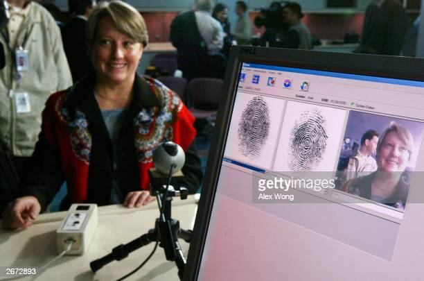 Penelope Smith of the USVISIT Program demonstrates the process of inkless fingerprints scanning during a news conference on the program October 28...