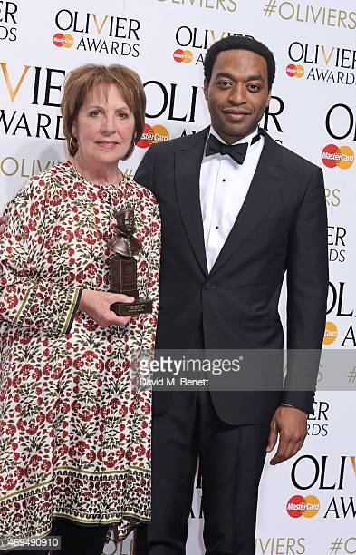 Penelope Wilton winner of the Best Actress award for 'Taken At Midnight' and presenter Chiwetel Ejiofor pose in the winners room at The Olivier...