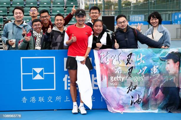 Peng Shuai of China poses with fans for photos during the women's doubles quarterfinal match against Irina Bara of Romania and Oksana Kalashnikova of...