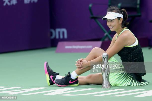 Peng Shuai of China poses with her trophy after winning the singles final match against Alison Riske of the US at the Tianjin Open tennis tournament...