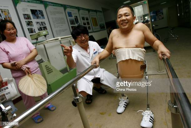 Peng Shuilin learns to walk as his wife and doctor look on at the China Rehabilitation Research Center on July 6 2007 in Beijing China 49yearold Peng...