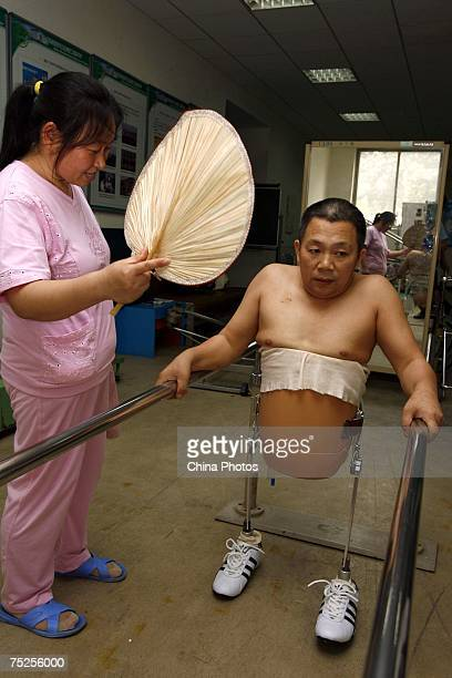 Peng Shuilin learns to walk as his wife looks on at the China Rehabilitation Research Center on July 6 2007 in Beijing China 49yearold Peng is...