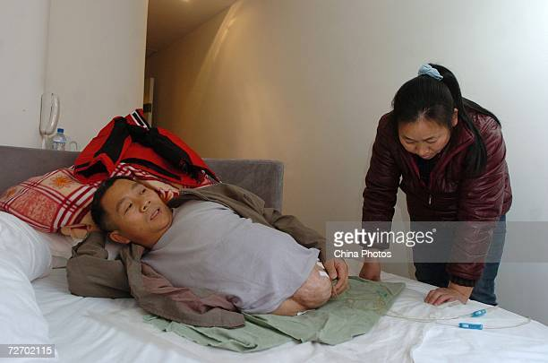 Peng Shuilin lies in the bed as his wife looks over his catheter at a hotel December 2 2006 in Beijing China Peng Shuilin was hit by a freight truck...